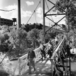 Workers crossing the footbridge spanning the Eau Claire River, 1947.